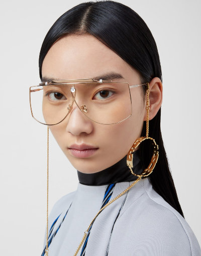 A woman wearing eyeglasses with a golden chain from Gentle Monster