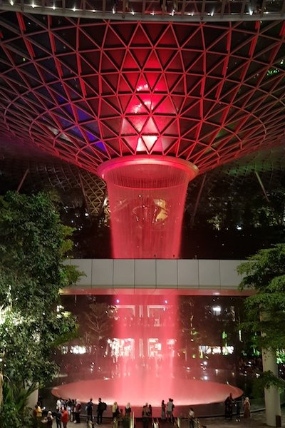 A tall indoor waterfall illuminated by red light and surrounded by greenery