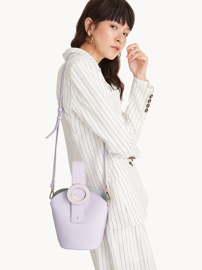 A woman wearing a white pinstripes dress has a lavender body bag slung over her shoulder