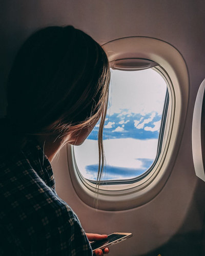A woman by the window inside a plane