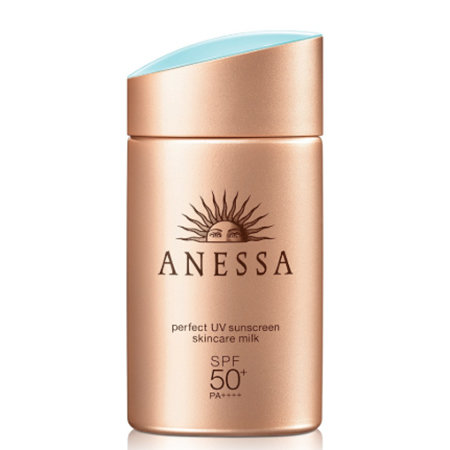 A bronze rectangular bottle of sunscreen, with an asymmetrical blue-topped cap.