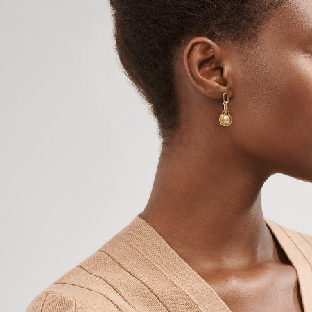 Woman wearing the gold pearl link earrings from Tiffany & Co
