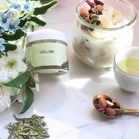 A jar of skincare surrounded by a cup of tea, plants, and yogurt