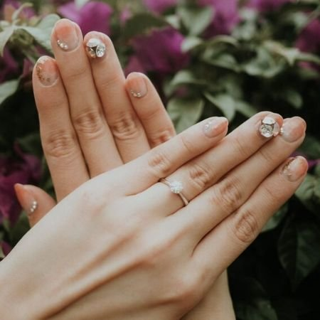 Bedazzled engagement nails with big nail gems and pink polish