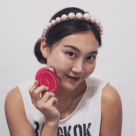 A girl wearing a headband using the Foreo Bear