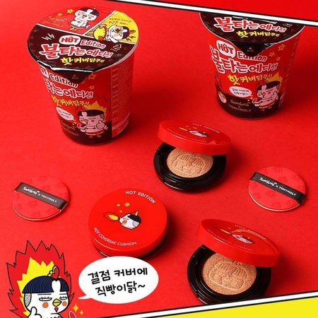 Red and black-cased cushion foundations and instant cup noodles are laid down on a red surface.