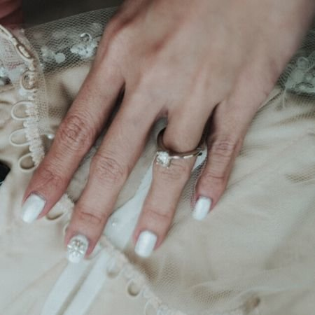 A hand with white-painted nails and holding a gown
