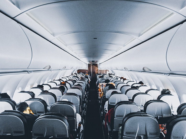 Rows of seats inside a plane and passengers surviving a long-haul flight
