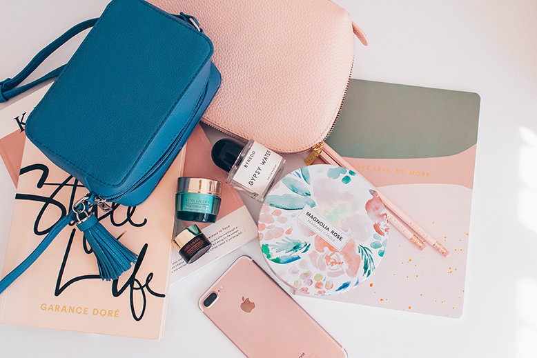 A bag, beauty products, and other accessories on a surface