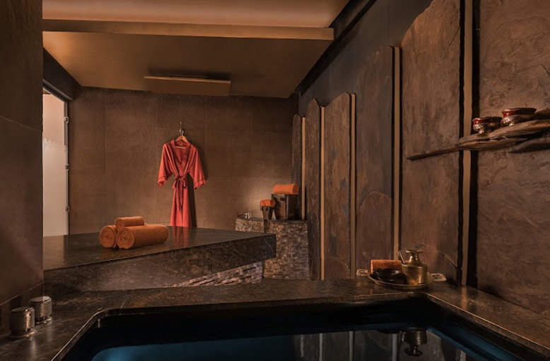 A pink bathrobe is hung in a marble and gold accented spa room with a water-filled tub