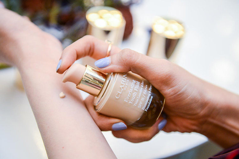 A woman putting a drop of Clarins Everlasting Youth Fluid, a liquid foundation, on her wrist