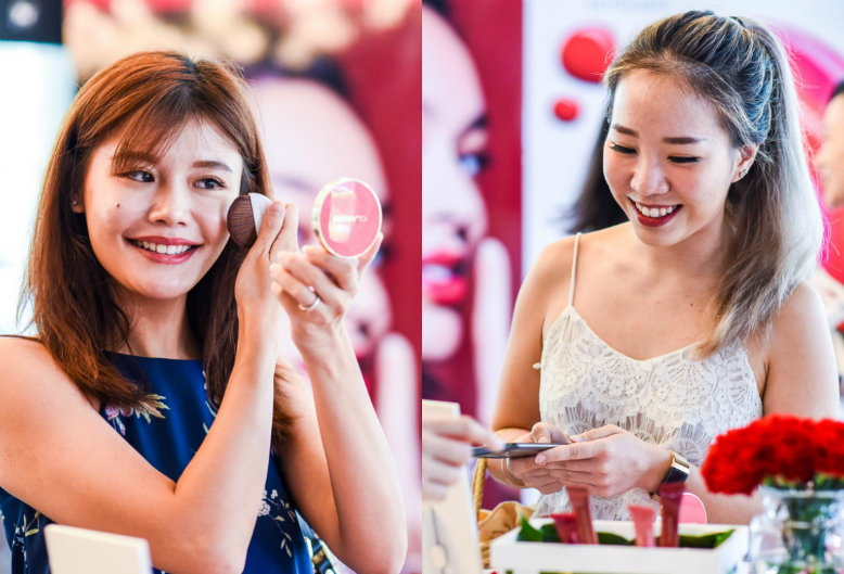 Women trying out different Clarins makeup products