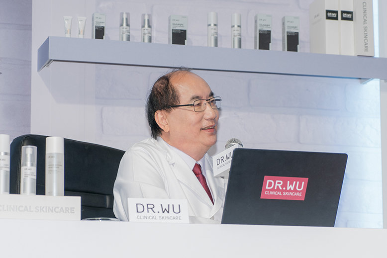 A dermatologist, tagged Dr. Wu, wears a white coat and glasses and sits behind a desk and a black laptop while speaking into a microphone.
