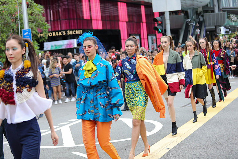 Models in a fashion show wearing colourful clothes