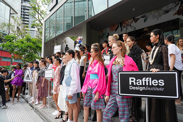Models standing on the front steps of Design Orchard