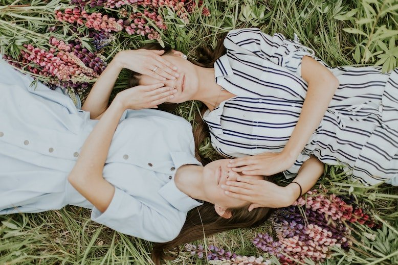 Two Girls Covering Faces Laying On A Field