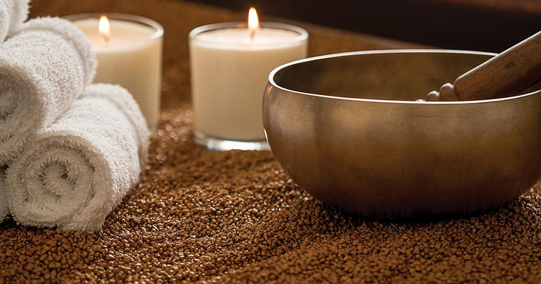 A golden bowl, two candles, and a bunch of towels atop golden quartz sand