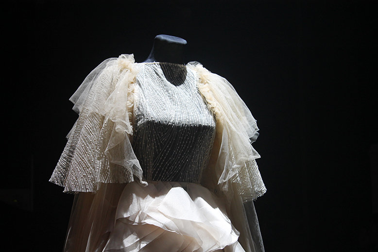 A closer look on elaborate embroidery and ruffles of a white gown