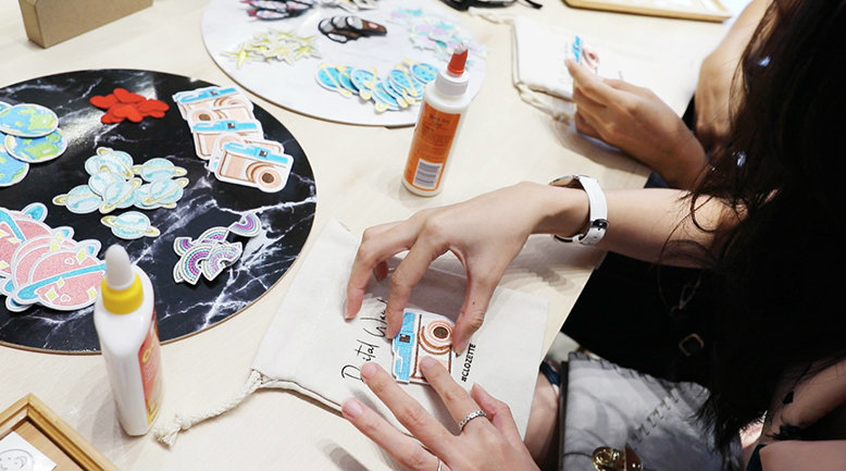 A woman customising her small canvas pouch with various designs.