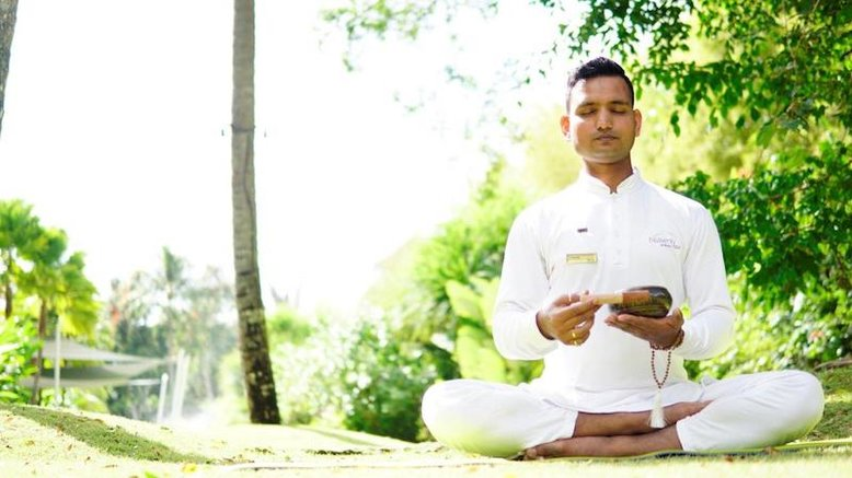 A man in white meditates surrounded by nature