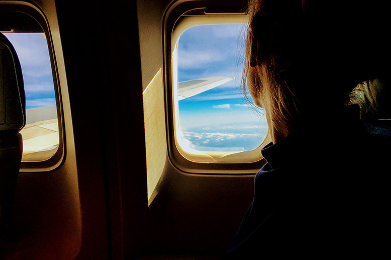 Woman looking out plane window during a long-haul flight