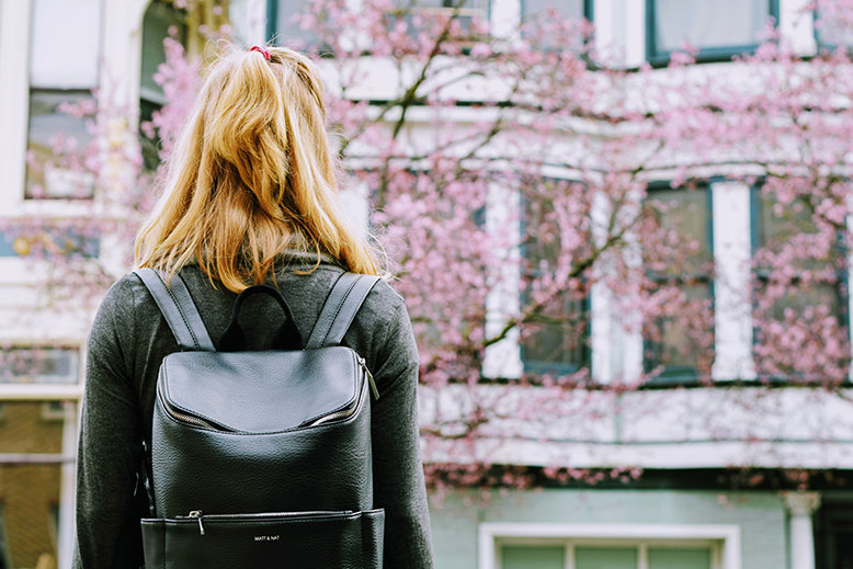 Back view of a woman with a black backpack facing a building