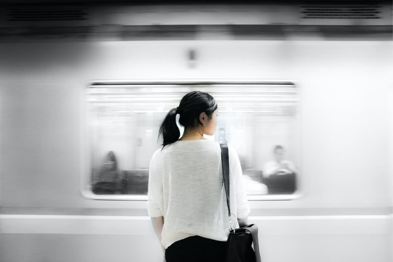A girl standing beside a moving train