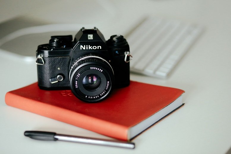 Nikon camera on red notebook with pen