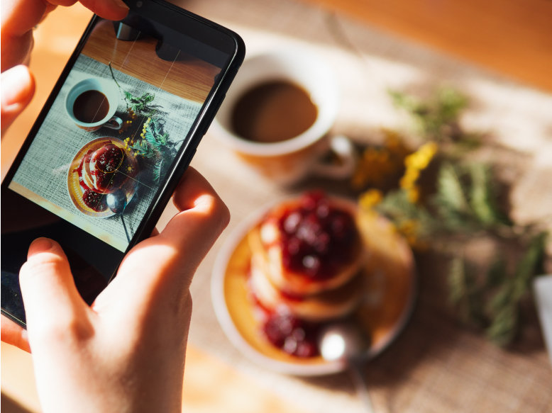 A mobile phone user captures a photo of Japanese pancakes with raspberry syrup