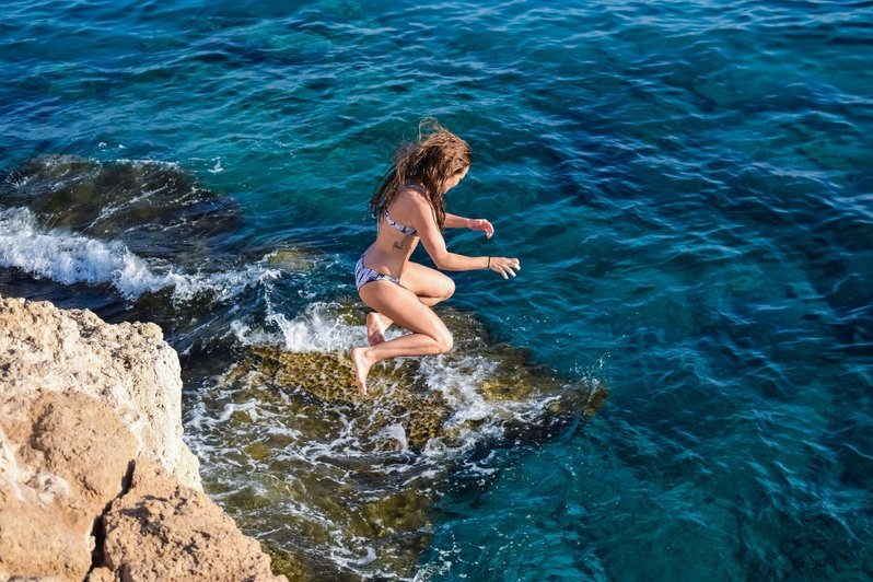 Woman jumping off a cliff into the sea