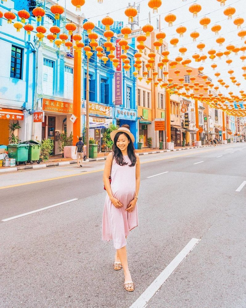 A pregnant lady wearing a pink tent dress is standing and smiling in the middle of a street lined with colourful shophouses and red Chinese lanterns