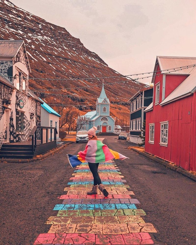 A woman wrapped in a rainbow scarf is walking on the rainbow path.