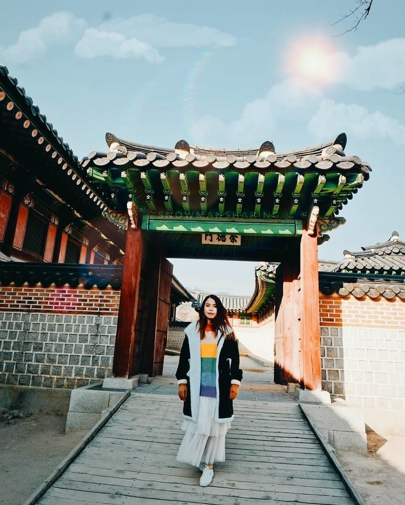 A woman standing in front of a traditional Korean gate is wearing a rainbow-striped shirt underneath her coat.