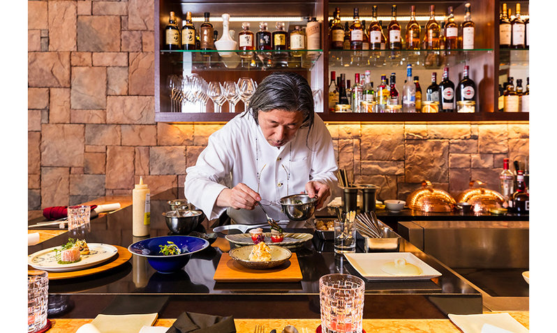 A Japanese chef, Masayasu Yonemura, arranges a dish on a plate.