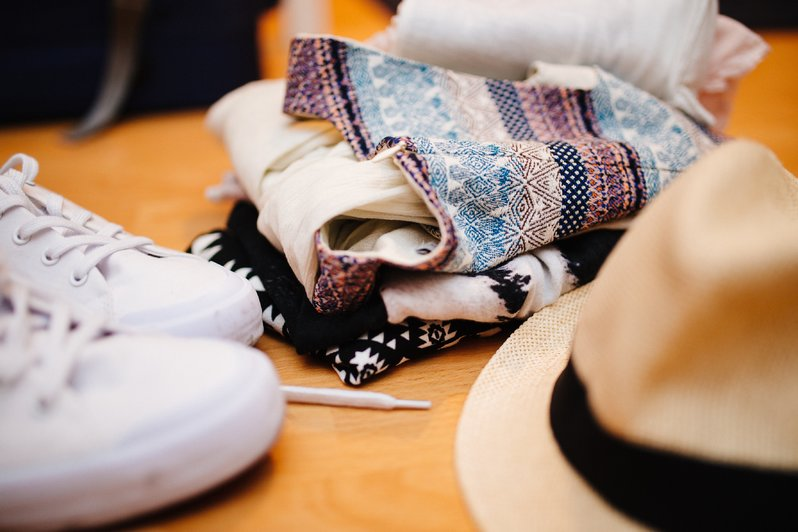 Folded clothes laying between white sneakers and a straw fedora