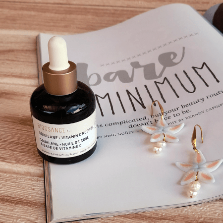 A photo of the Biossance Squalane & Vitamin C Rose Oil with a magazine and earrings