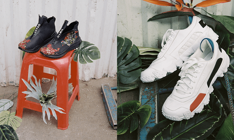 On the left is a pair of black high-cut sneakers with russian floral art details placed on top of a stool. On the right is a pair of white sneakers with rubberised colour-blocked panels.