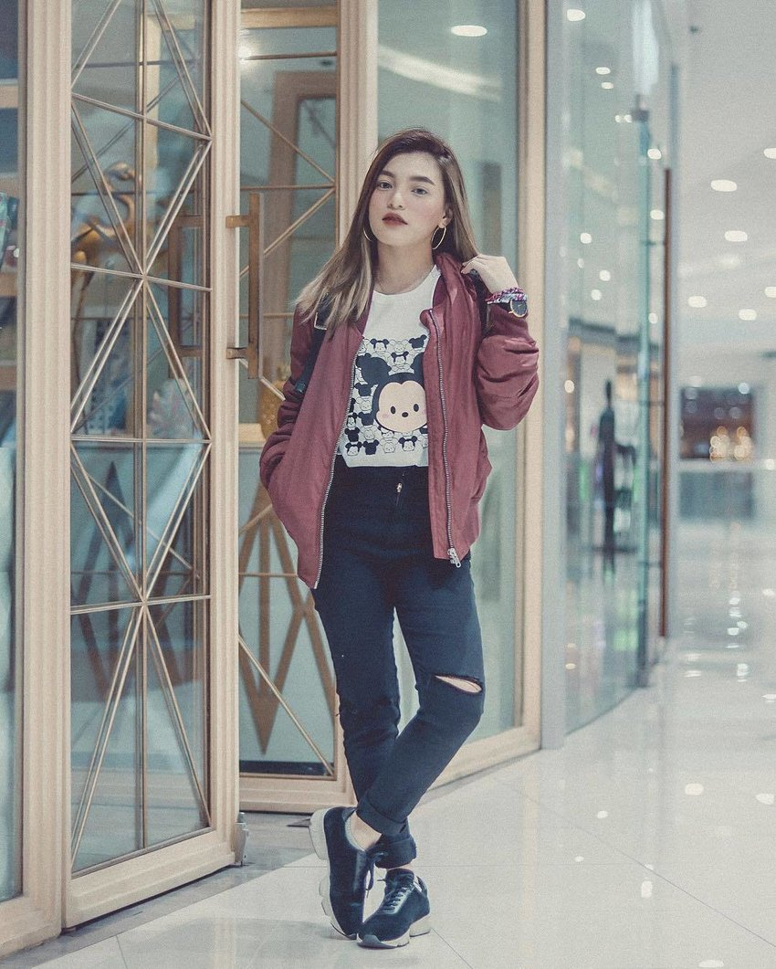 A woman wears a Mickey Mouse shirt with maroon bomber jacket and ripped jeans