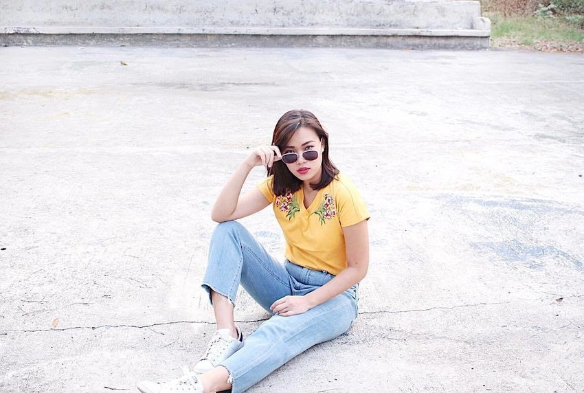 Woman wearing mustard blouse and jeans