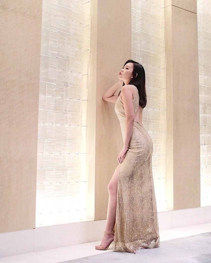 A woman faces the wall, revealing the backless detail of her shimmering gown.