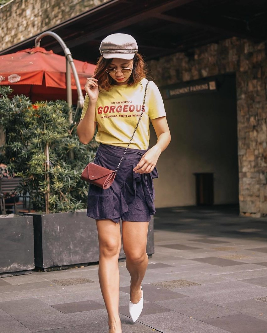 A woman is wearing a yellow graphic tee and a blue wrap skort
