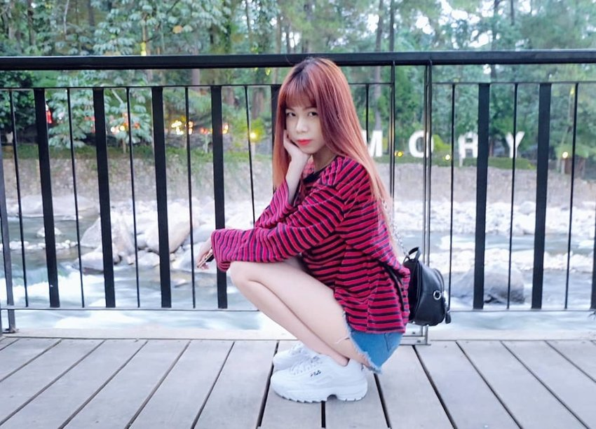 A woman wears striped sweater with frayed shorts