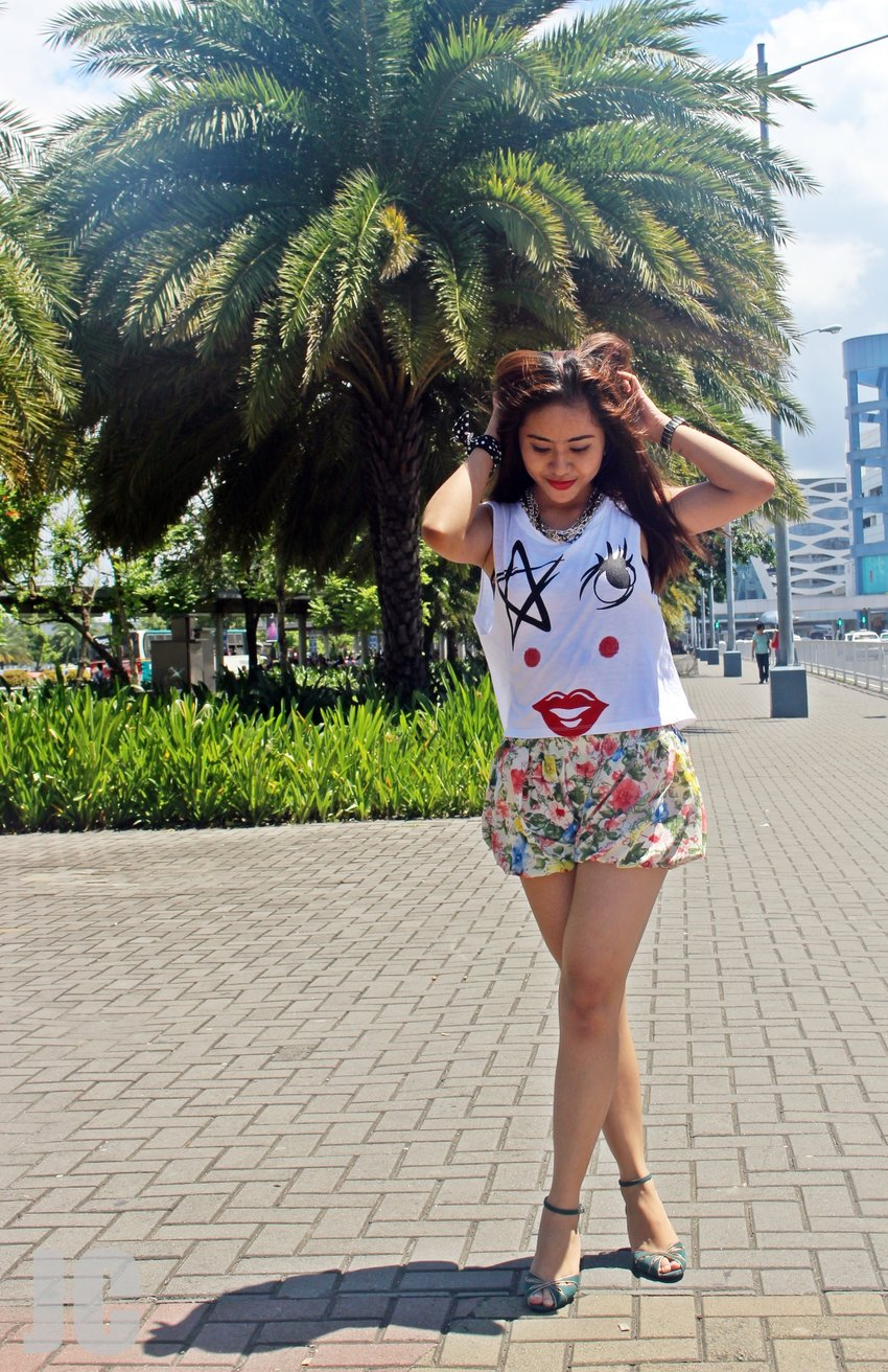 A woman wears a white sleeveless graphic crop top with yellow floral shorts