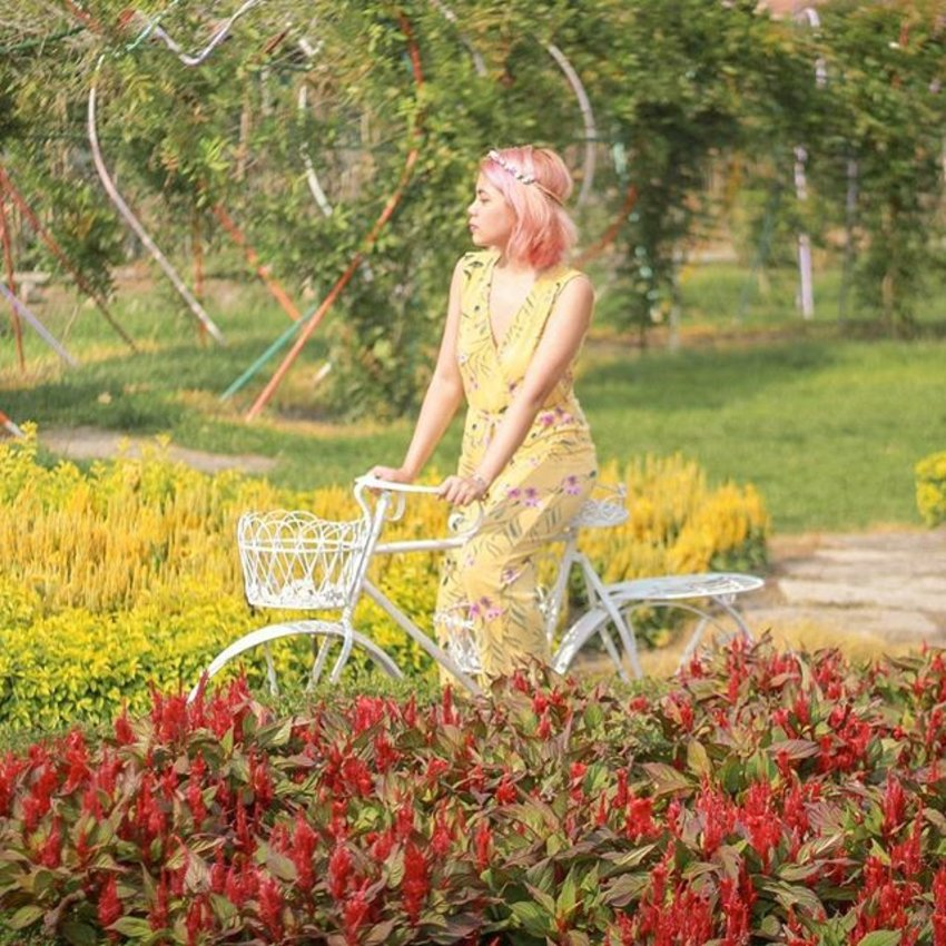 A woman biking through flower fields wears a yellow tropical print maxi dress